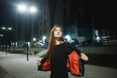 Mysterious redhead woman in elegant leather jacket coat and high heels walking in city street, noire atmosphere. Intriguing people concept royalty free stock photography
