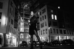 Mysterious redhead woman in elegant leather jacket coat and high heels walking in city street, noire atmosphere. Intriguing people concept royalty free stock photo