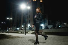 Mysterious redhead woman in elegant leather jacket coat and high heels walking in city street, noire atmosphere. Intriguing people concept stock image