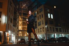 Mysterious redhead woman in elegant leather jacket coat and high heels walking in city street, noire atmosphere. Intriguing people concept stock photo