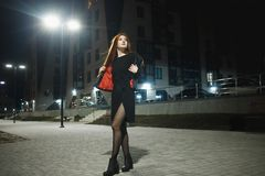 Mysterious redhead woman in elegant leather jacket coat and high heels walking in city street, noire atmosphere. Intriguing people concept royalty free stock photos