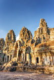 Mysterious ruins of ancient Bayon temple, Angkor Thom, Cambodia. Mysterious ruins of ancient Bayon temple on blue sky background. Enigmatic Bayon nestled in Stock Photography