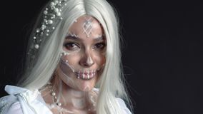 Mysterious sea mermaid with white long straight hair smiles at camera. Lady with pearl jewelry in her hair and necklace, on her face, dead spirit with bone stock footage