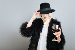Mysterious senior woman drinking wine. Royalty Free Stock Photos