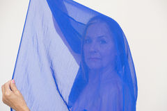 Mysterious serious lady behind blue cloth Stock Photo