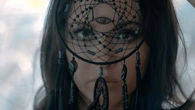 Mysterious woman with make up looking through black dream catcher