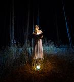 Mysterious shot of woman reading big book at dark forest Stock Photos