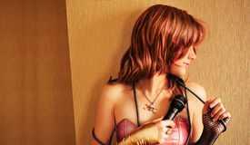 Mysterious Singer. Beautiful red-haired girl with microphone in her hand Royalty Free Stock Image
