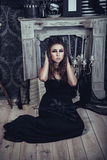 Mysterious sitting young girl in black haloween dress Royalty Free Stock Photo