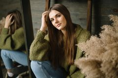 Mysterious smiling young girl in dark green knitted cozy sweater with the sheaves of hay composition and mirror. Mysterious smiling young girl in dark green stock photography