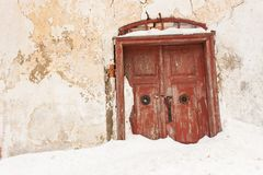 Mysterious snowy old wooden red door. Mysterious entrance to the house. Royalty Free Stock Photo