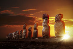 Mysterious stone statues at dramatic sunrise. Mysterious stone statues at dramatic orange sunrise in Easter Island royalty free stock photo