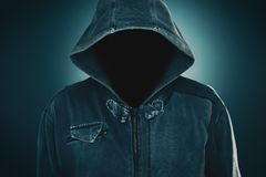 Mysterious suspicious faceless man with hoodie. Dark low key portrait for crime and violence concepts stock images
