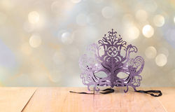Mysterious Venetian masquerade mask on wooden table and glitter background Stock Image