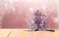 Mysterious Venetian masquerade mask on wooden table and glitter background. Royalty Free Stock Photo