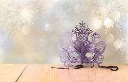 Mysterious Venetian masquerade mask on wooden table and glitter background Royalty Free Stock Image