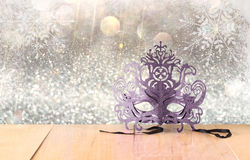 Mysterious Venetian masquerade mask on wooden table and glitter background. Royalty Free Stock Photography