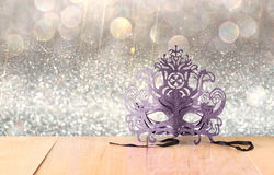 Mysterious Venetian masquerade mask on wooden table and glitter background. Stock Photo