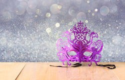 Mysterious Venetian masquerade mask on wooden table and glitter background Royalty Free Stock Images