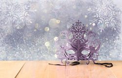 Mysterious Venetian masquerade mask on wooden table and glitter background with snowflake overlays Stock Image