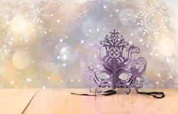 Mysterious Venetian masquerade mask on wooden table and glitter background with snowflake overlays Royalty Free Stock Images