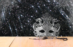 Mysterious Venetian masquerade mask on wooden table and glitter vintage lights background. light silver and black Stock Image
