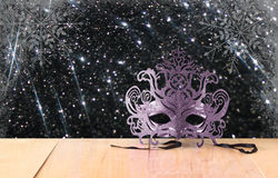 Mysterious Venetian masquerade mask on wooden table and glitter vintage lights background. light silver and black Stock Photo