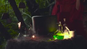 Mysterious video, forest sorceress makes potion in seething cauldron stock video