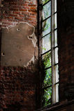 Mysterious window in an old brick building with a lot of green outside Stock Image