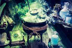 Mysterious witch pot with blue potions and books for Halloween Stock Photos