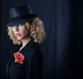 Mysterious woman. Portrait of a young mysterious woman in black hat on a dark background Stock Photography