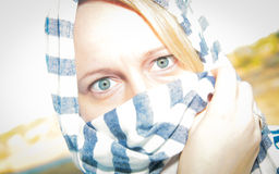 Mysterious Woman. A beautiful and mysterious woman with blue eyes, face hidden by a striped scarf Royalty Free Stock Images