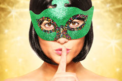 Mysterious woman. A portrait of a beautiful mysterious woman hiding her face behind carnival mask Stock Photography