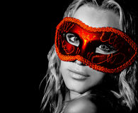 Mysterious woman. Wearing decorative face mask, girl at holiday party celebration, female in red light isolated on black background, New Year and Christmas stock photo