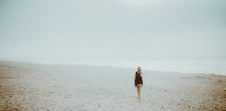 Mysterious woman at mysterious beach. Cute blonde girl is standing alone at the foggy beach Stock Images