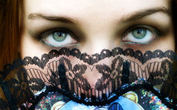 Mysterious woman with beautiful eyes and fan royalty free stock images
