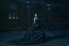 Mysterious woman in black dress near chirch. Woman in black gothic dress near chirch Royalty Free Stock Photo