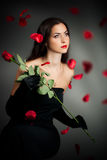 Mysterious woman in dark hood with rose Royalty Free Stock Photos