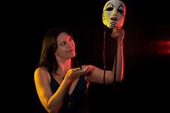 Mysterious woman holds up her mask Stock Photo