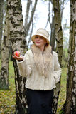 The mysterious woman keeps decorative apple on a palm in a hat Stock Photos
