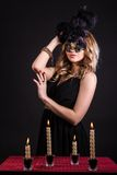 Mysterious woman in a mask near the table with alight candles. Over black background Royalty Free Stock Photography