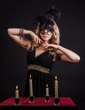 Mysterious woman in a mask near the table with alight candles. Over black background Stock Photos