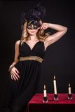 Mysterious woman in a mask near the table with alight candles. Over black background Royalty Free Stock Image