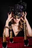 Mysterious woman in a mask near the table with alight candles. Over black background Royalty Free Stock Images