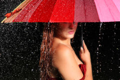 Mysterious Woman in the Rain. Beautiful sexy wet red head woman standing in the rain holding an umbrella with the umbrella covering her eyes Royalty Free Stock Photography