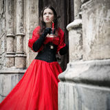 Mysterious woman in red Victorian dress stock photography