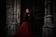 Mysterious woman in red Victorian dress. With a candle royalty free stock photo