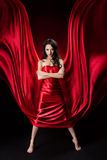 Mysterious woman in red waving silk dress. Over black background stock photo