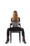 Mysterious woman sitting on a black chair. Mysterious woman with her face covered by her hair is sitting on a black chair - isolated on white Royalty Free Stock Photos