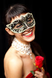 Mysterious woman smiling, wearing a  mask. Mysterious woman  smiling ,wearing a  mask, holding a red rose, studio shot Stock Images